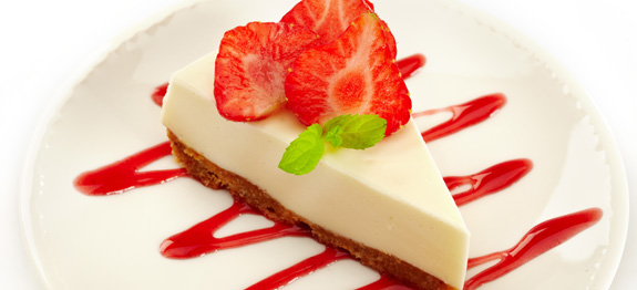cheesecake with strawberries on white plate